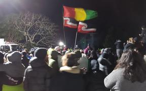 Flags fly at Ihumatao on Monday evening after police ramped up their presence.