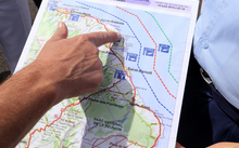 French maritime gendarmes look at a map indicating measures being undertaken in the search for wreckage from the missing MH370 plane at the marina of Saint-Marie on the French island of La Reunion on August 14, 2015.