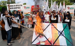 Activists of the Youth Forum for Kashmir group shout slogans as they burn a picture of Indian Prime Minister Narendra Modi and the Indian flag during a protest in Lahore.