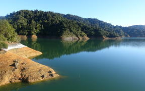 Mangatangi Dam (Watercare's largest dam), showing low water levels, in the Hunua Ranges.