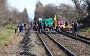 30 Extinction Rebellion members sat on the train tracks in Woolston near Christchurch on Friday, 9 August.