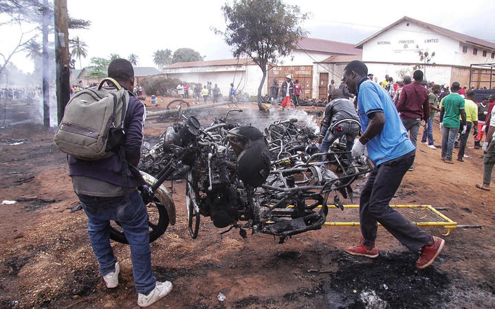 Two men carry the remains of a burnt out motorbike after a fuel tanker exploded on August 10, 2019, in Morogoro.