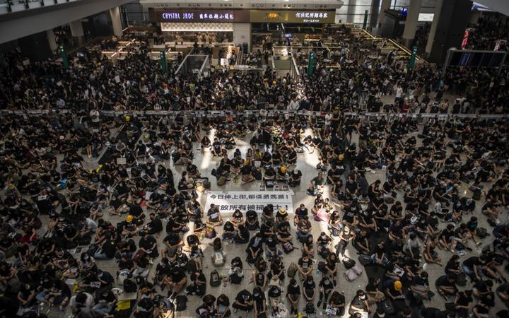 Protesters are seen sitting in the arrival hall in Hong Kong International Airport in Hong Kong.