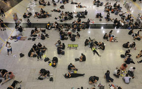 Protesters sit on the floor of the arrivals hall of Hong Kong's international airport.