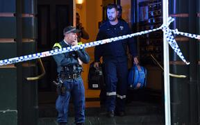 Police investigate inside a building near the scene of a knife rampage in Sydney.