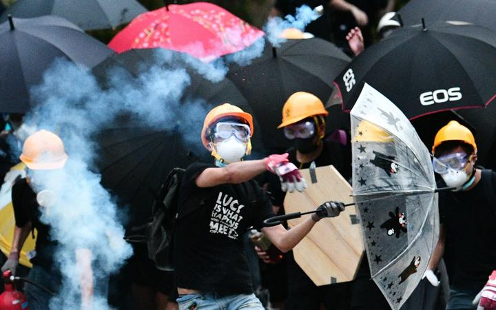 A protester throws back a round of tear gas fired by the police during a demonstration in the district of Yuen Long in Hong Kong on July 27, 2019.