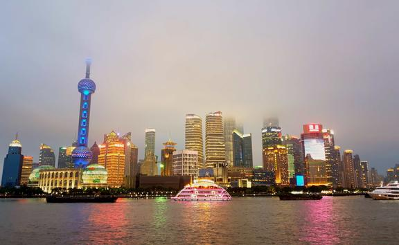 Tall buildings and night time lights of Shanghai from across the water.
