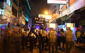 Policemen secure a street after dispersing pro-democracy protestors in the Sham Shui Po Area of Hong Kong.