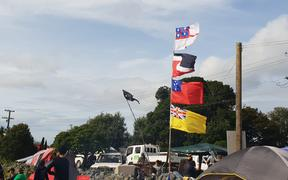 There are a range of flags on show, including (from top to bottom) the United Tribes of New Zealand flag, the tino rangatiratanga flag, the Samoan flag and the Nuienan flag, to represent the unity of all nations.