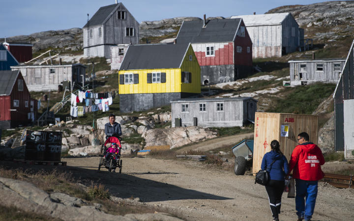 People walking in Kulusuk, Greenland.
