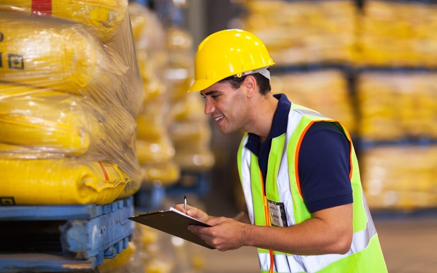 A warehouse worker wearing a high-vis vest holds a clipboard (file).