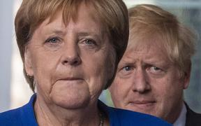 German Chancellor Angela Merkel (L) and British Prime Minister Boris Johnson arrive for a press conference at the Chancellery.