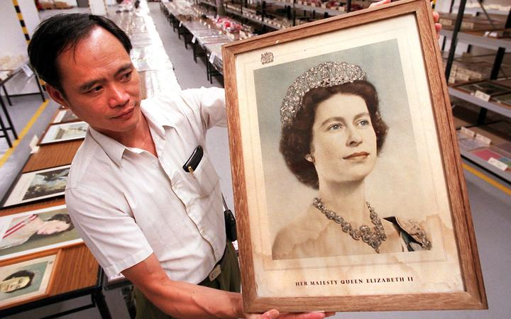 Senior Supplies Supervisor Lin Pong-yin holds up a stained portrait of Queen Elizabeth II 17 October,  which was among nearly 10,000 items bearing connotations of British sovereignty that were to be auctioned to the public.