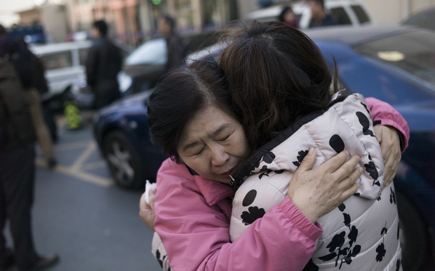 Two relatives of Chinese passengers aboard missing Malaysia Airlines flight MH370 cry as they leave the Beijing Rail Transportation Court in Beijing on March 7, 2016.