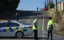 A section of Coast Road is closed after a woman was found dead inside a property.