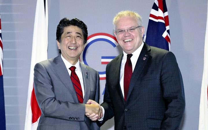 Australia's Prime Minister Scott Morrison shakes hands with Japan's counterpart Shinzo Abe ahead of their summit meeting during the G7 summit meeting in Biarritz.