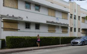 A woman walks by a building with boarded up windows during a hurricane alert for this weekend in South Miami Beach, Florida.