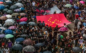 Protesters march with a banner that uses the stars of the Chinese national flag to depict a Nazi Swastika symbol in the Central district of Hong Kong.