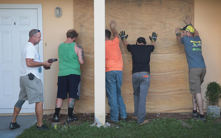 Workers help a friend board up his apartment building in Fort Pierce, Florida.