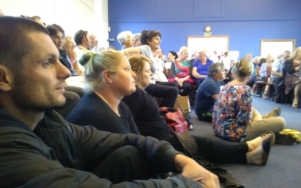 Paul Chronis and Charlotte Boocock sit on the church hall floor at a packed Island Bay meeting.