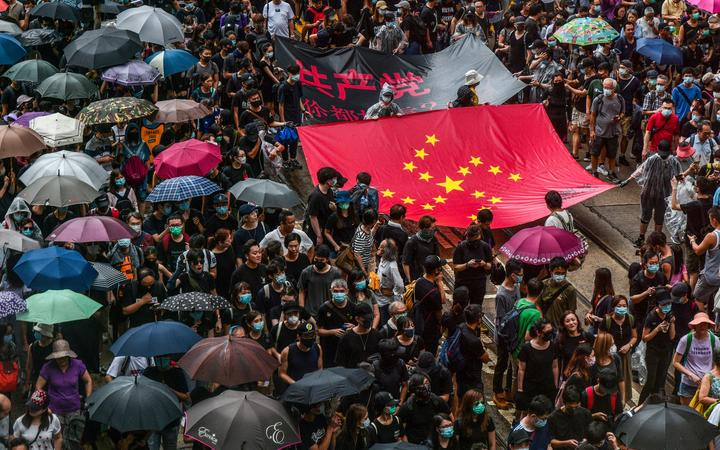 Protesters march with a banner that uses the stars of the Chinese national flag to depict a Nazi Swastika symbol in the Central district of Hong Kong on August 31, 2019.