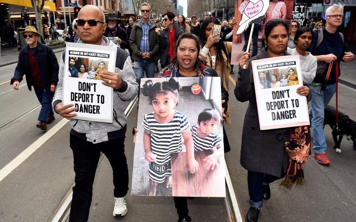Protesters holds up placards in Melbourne on September 1 during a rally in support of a Tamil refugee family of four -- including two Australian-born toddlers -- who have been moved to the remote Australian detention centre on Christmas Island.