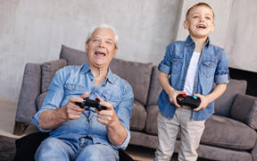A photo of a boy teaching his father or grandfather how to game using a gaming controllers.