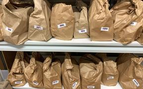 brown paper bags with numbers labels sit on a shelf