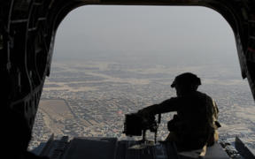 A file photo of a soldier in a helicopter flying over Kabul.