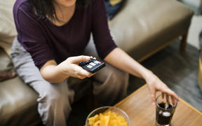 Woman sitting at home on couch, snacking, eating, and watching television.