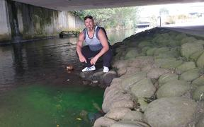 Aaron Tainui at the site of a luminous green discharge into the Huatoki Stream.