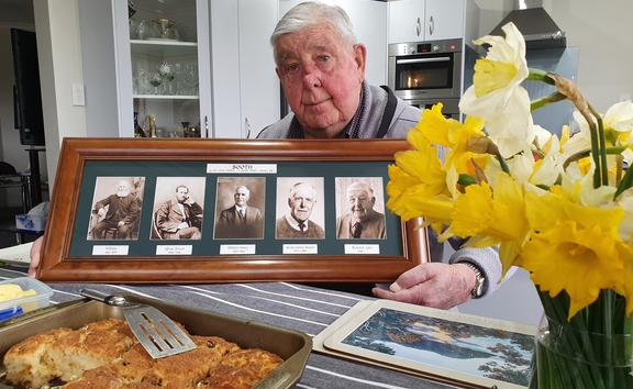 Dick Booth of Middlerun Farm with photos of his forebears who planted the daffodils the property is famous for