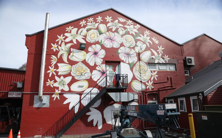 Artist Paul X Walsh has painted 51 flowers on the side of Pomeroys Inn in Christchurch as a mural for the victims of the March 15th Mosque Attack.