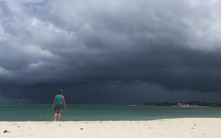 A woman walks on the beach as a storm approaches in Nassau, Bahamas.