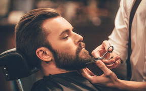 Close-up side view of young bearded man getting beard at barber shop.