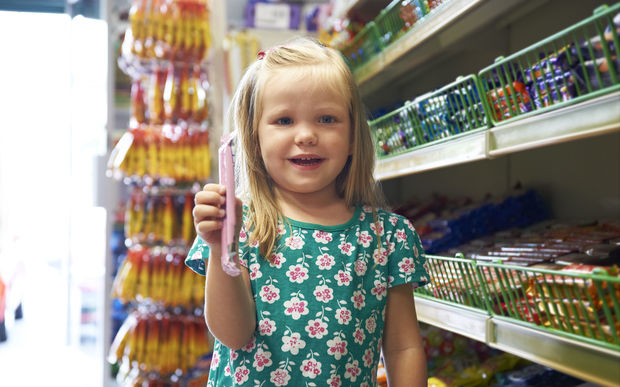 A little girl with a big smile stands next to the lolly aisle at a supermarket (file)