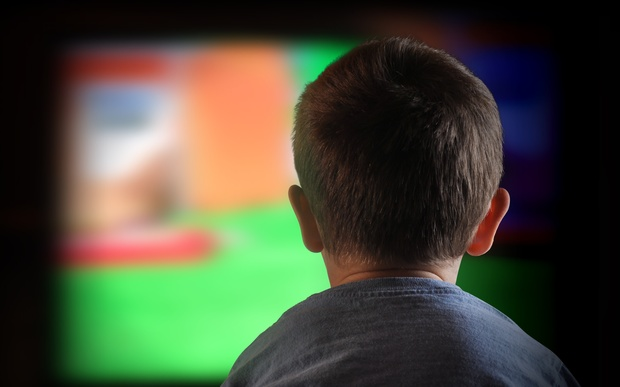 A close-up of a child watching television
