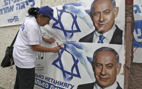 A woman places electoral banners for the Likud party showing Israeli Prime Minister Benjamin Netanyahu, in the southern Israeli city of Beersheva on 15 September 2019.