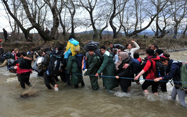 Refugees formed a human chain across the river to help people cross into Macedonia.