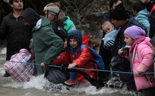 Refugees cross a river on their way to Macedonia from a makeshift camp at the Greek-Macedonian border.