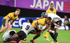 Australian prop Scott Sio tries to bust through the tackle in the World Cup match against Fiji.