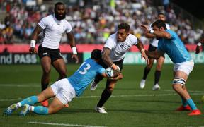 Fiji's centre Jale Vatubua (C) is tackled by Juan Manuel Cat (L) and flanker Santiago Civetta (R).