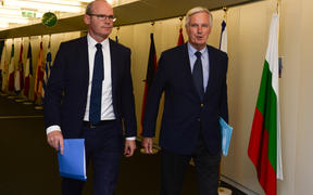 Irish Foreign Minister Simon Coveney (left) arrives to meet with European Union's chief Brexit negotiator Michel Barnier at the EU Commission headquarters in Brussels yesterday.