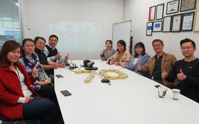 Chinese employees gather in Auckland to live stream China's national day parade.