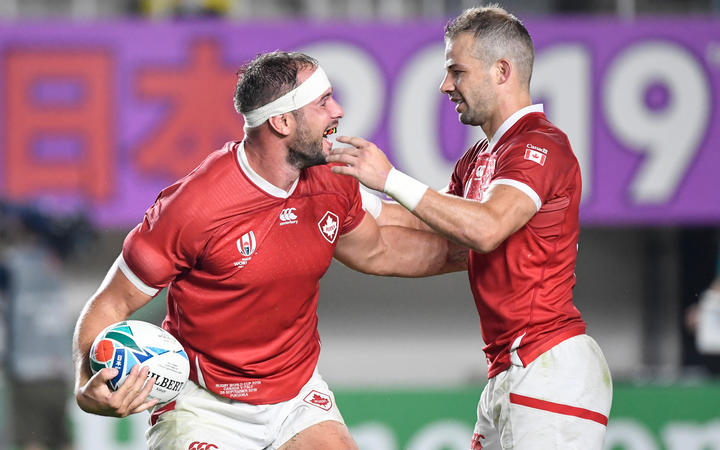 Canada's number 8 Tyler Ardron (L) celebrates his try that was later disallowed with Canada's scrum-half Gordon McRorie during the Japan 2019 Rugby World Cup Pool B match between Italy and Canada at the Fukuoka Hakatanomori Stadium in Fukuoka on September 26, 2019. (Photo by CHRISTOPHE SIMON / AFP)