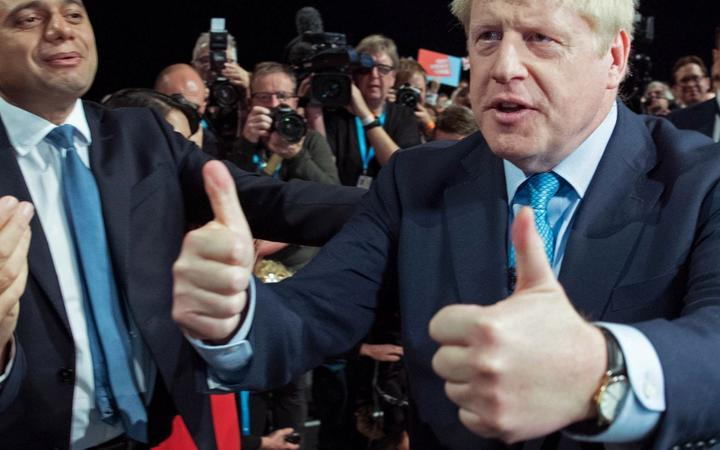 Boris Johnson acknowledges the applause from  members of his cabinet as he leaves after delivering his keynote speech on the final day of the annual Conservative Party conference.