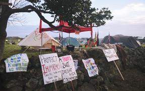 Protest signs and tents at Ihumātao.