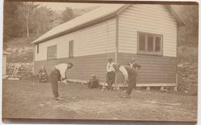 Patients playing 'clock golf' in front of the unused recreation hall: from left, Will Vallance, Jim Kokiri, Ah Yip, Jim Lord, Ipirini Apa Apa and Ivon Skelton. Other pastimes included gardening, chopping wood, playing billiards and reading. Photograph c.1923, Lyttelton Museum