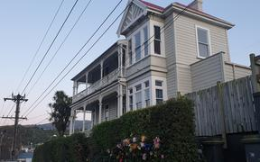 Flower bouquets have been left outside a house on Dundas Street, Dunedin, where a university student died after being fatally hurt at an overcrowded part.