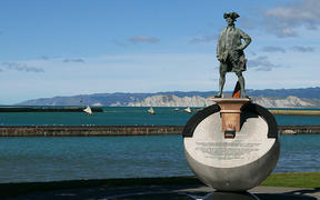 Cook and Vaka - a flotilla of sailing va'a cruise offshore of a statue of James Cook on the Gisborne foreshore